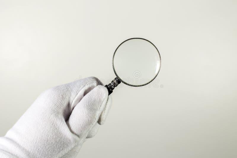 Luva branca que guarda a lente de aumento imagens de stock royalty free