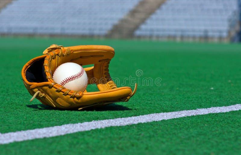 Luva de beisebol e bola no campo fotografia de stock
