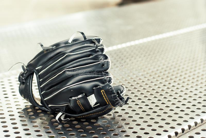 Luva de beisebol preta colocada no banco de aço inoxidável imagens de stock