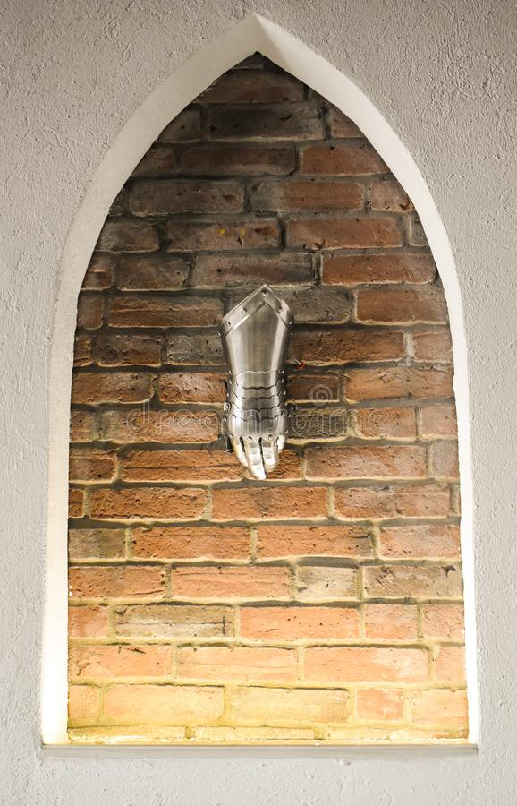 Luva de metal medieval, detalhe de pe?a da armadura antiga, detalhe de guerra Luva de brilho do ferro contra o fundo da parede de imagem de stock royalty free
