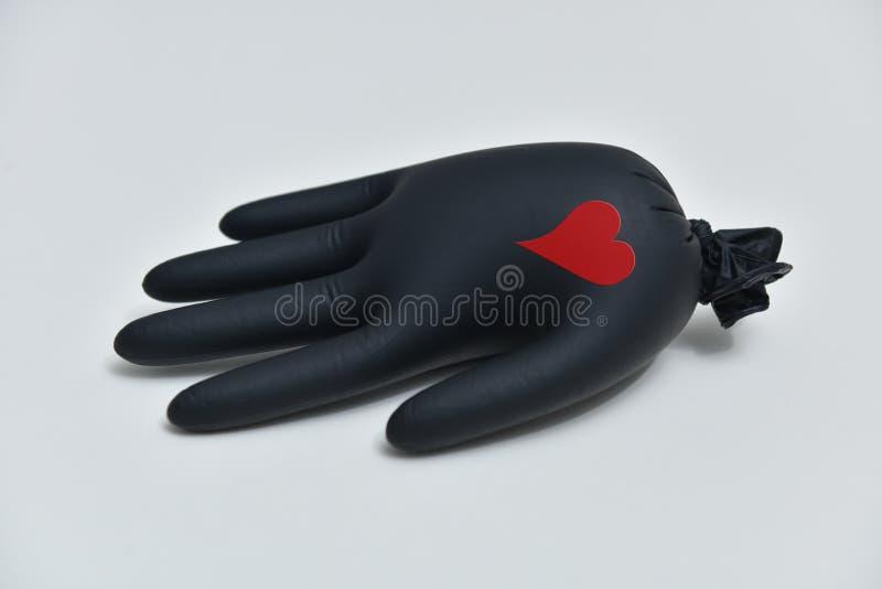 Luva preta com coração Conceito de coronavírus Luva negra solitária fotografia de stock