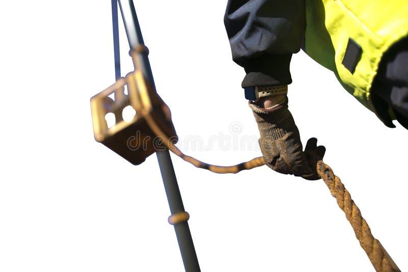 Luva resistente vestindo de começo do trabalhador do Rigger que guarda uma linha de etiqueta corda da segurança para controlar um fotos de stock royalty free