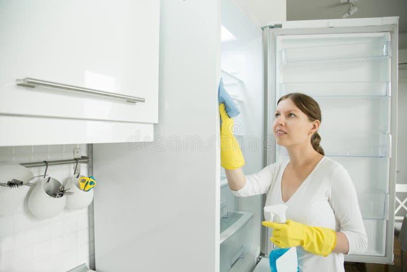 Luvas de borracha vestindo da jovem mulher que limpam o refrigerador imagens de stock royalty free
