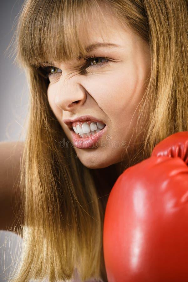Luvas de encaixotamento desgastando da mulher irritada foto de stock