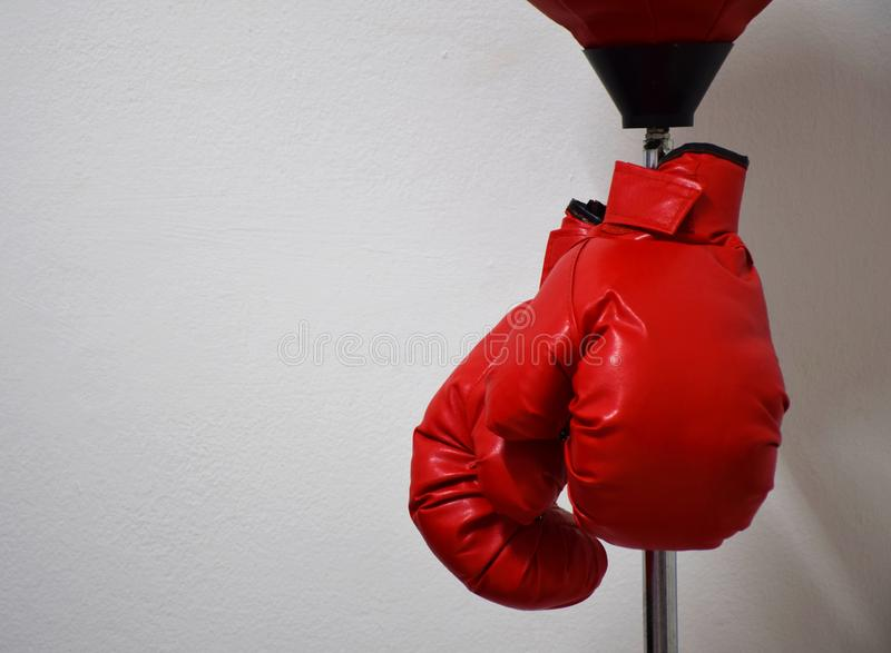 Luvas de encaixotamento vermelhas que penduram no polo da bola de perfuração no muro de cimento foto de stock royalty free