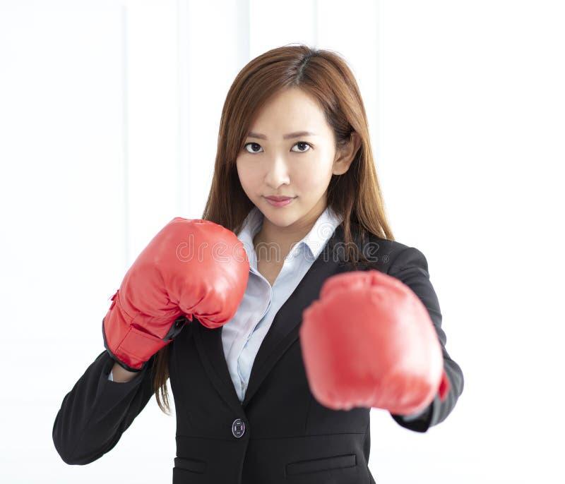 Luvas de encaixotamento vestindo da mulher de negócio prontas para lutar foto de stock