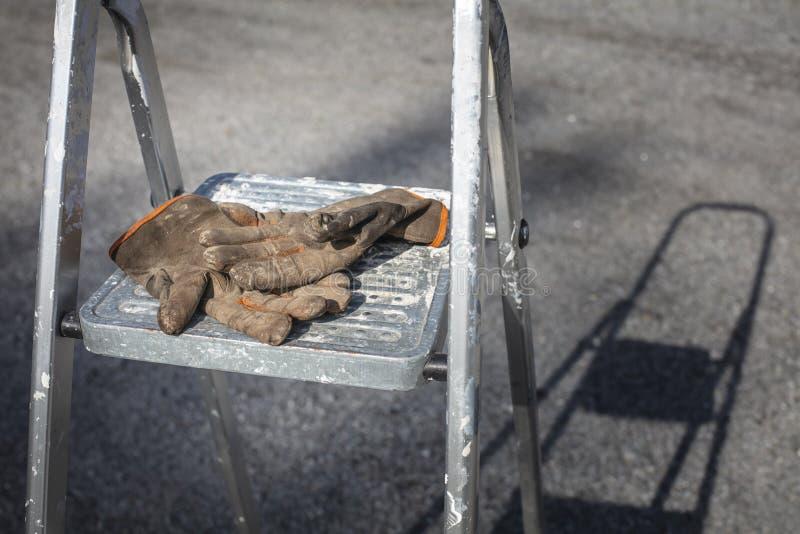 Luvas de trabalho usadas e sujas em escadas na Finlândia fotografia de stock