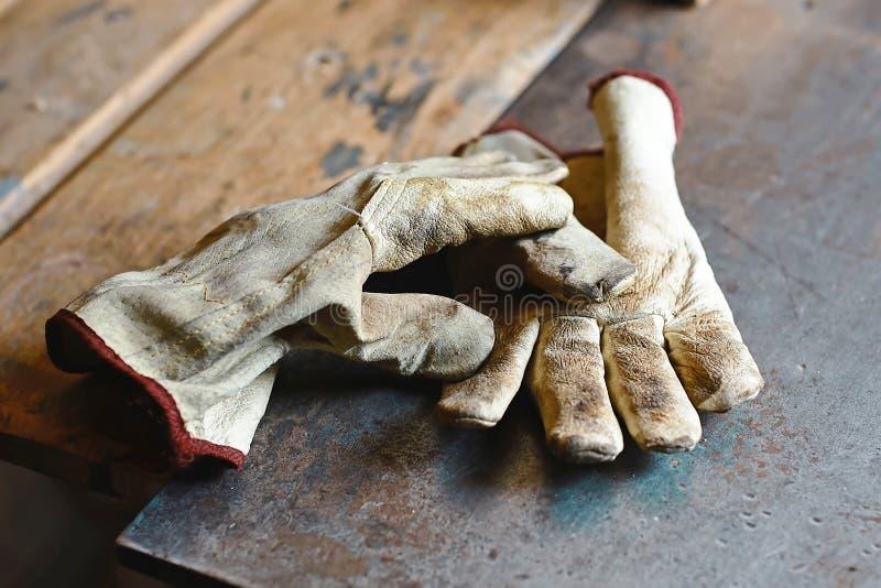 Luvas de trabalho velhas sobre a tabela de madeira, em ferramentas de uma construção da máquina do woodworking do metal, luvas pa fotografia de stock