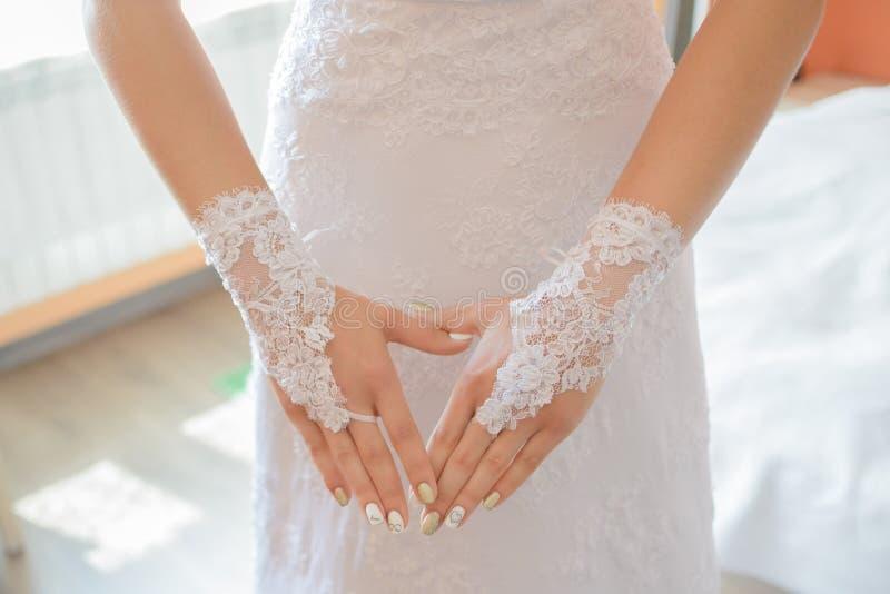 Luvas do casamento nas mãos da noiva fotografia de stock