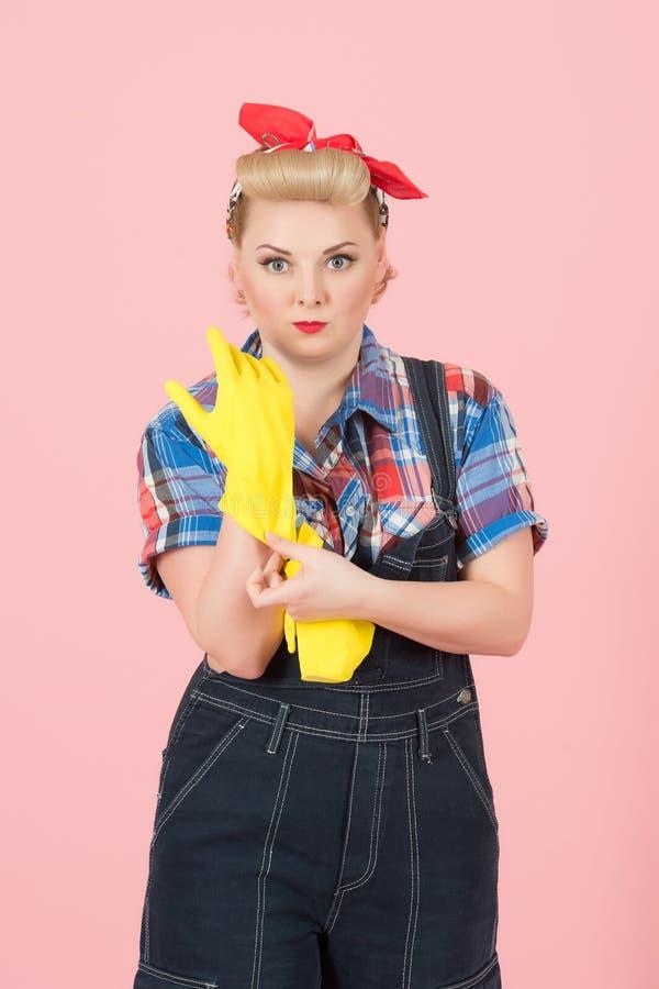 Luvas do látex da tomada disponível! Dona de casa nova loura que toma em luvas amarelas do látex antes de limpar Conceito moderno fotos de stock
