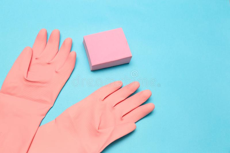 Luvas e esponja cor-de-rosa no fundo azul imagem de stock
