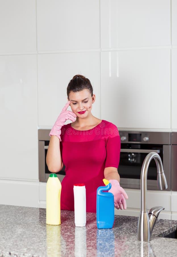 Luvas vestindo da limpeza da mulher que estão em uma cozinha fotos de stock royalty free