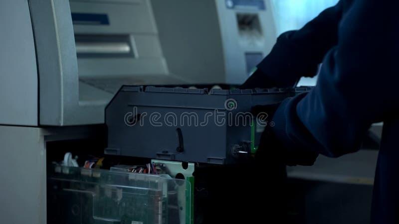Luvas vestindo do ladrão que roubam o dinheiro das caixas do ATM na noite, insegurança imagens de stock