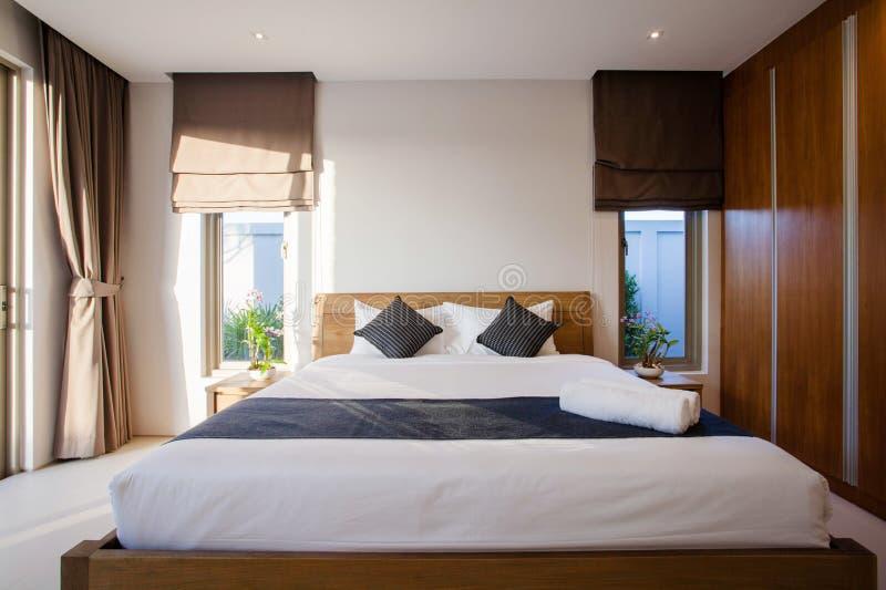 Luxe Binnenlands ontwerp in slaapkamer van poolvilla met comfortabel bed met hoog opgeheven plafond in het huis of huisgebouw royalty-vrije stock afbeeldingen
