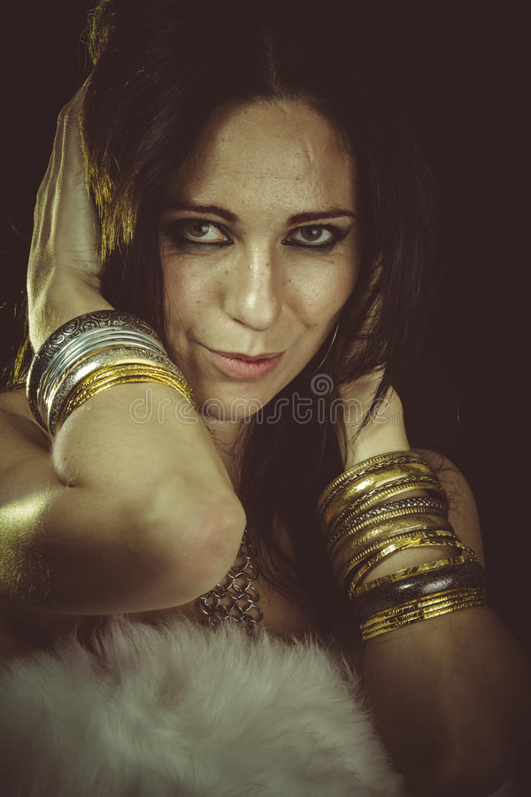 Luxe, donkerbruine vrouw die wit bont en gouden juwelen dragen stock fotografie