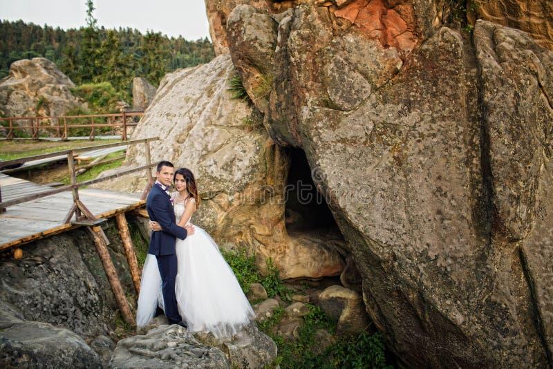 Luxe gelukkige bruid en modieuze bruidegom die elkaar met tien koesteren stock foto's