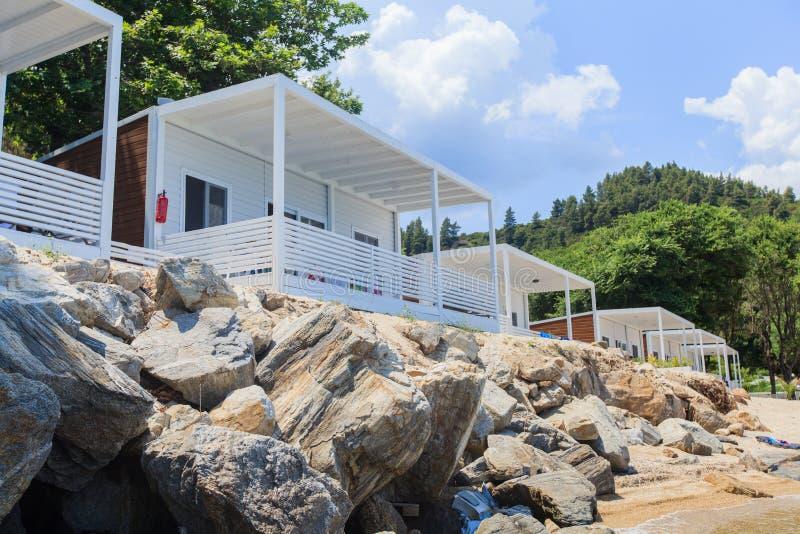 Luxe houten witte bungalowwen op rotsenstrand royalty-vrije stock afbeelding