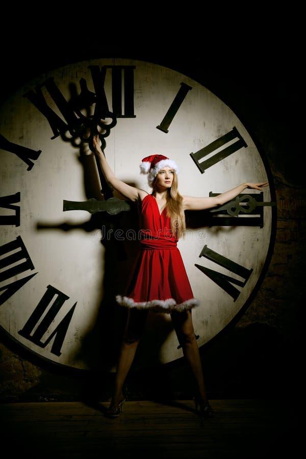 Luxe jonge vrouw in Kerstmankostuum op de grote wijzerplaat Meisje en cl stock afbeelding