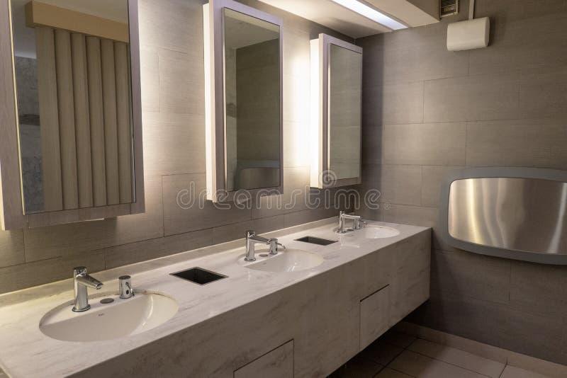 Luxe marmeren bassin met licht in spiegel in openbaar toilet stock fotografie
