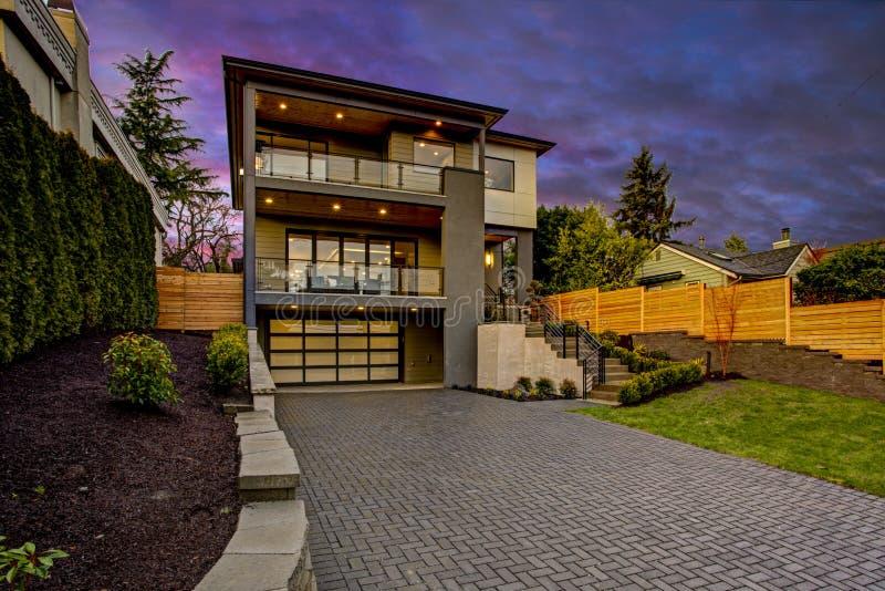 Luxe modern huis buiten bij zonsondergang stock afbeeldingen