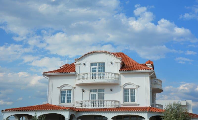 Luxe modern huis met zolderbalkon en het rode dak van kleitegels stock fotografie