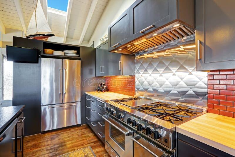Luxe mooie donkere moderne keuken met gewelfd houten plafond royalty-vrije stock foto
