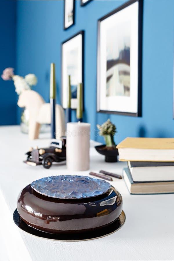 Luxe om chocoladedessert, met een blauwe schijf op Zwarte glans De cake van de mousseverjaardag met decor Op een houten lijst royalty-vrije stock foto's