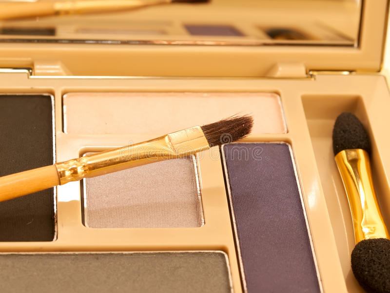 Luxe purple and beige make-up eyeshadows in gold packing. Studio stock images