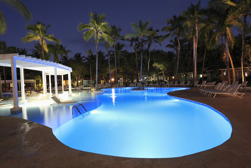 Luxe Tropisch die zwembad bij nacht wordt verlicht stock foto