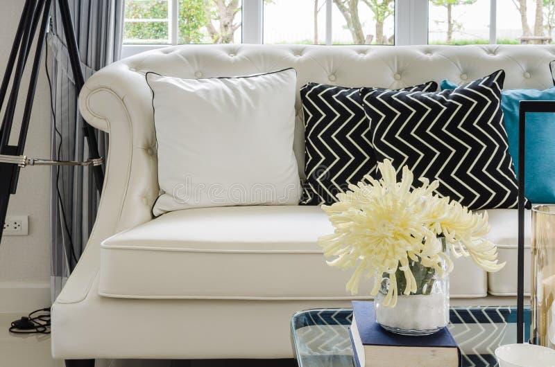 Luxe witte bank in woonkamer met gele bloem in vaas stock foto's