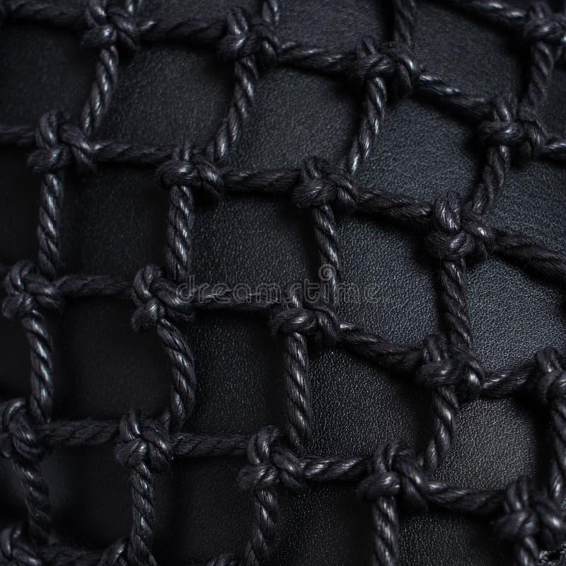 Luxe zwart die leer met zwarte netto kabel wordt behandeld Mooie achtergrond close-up stock afbeelding