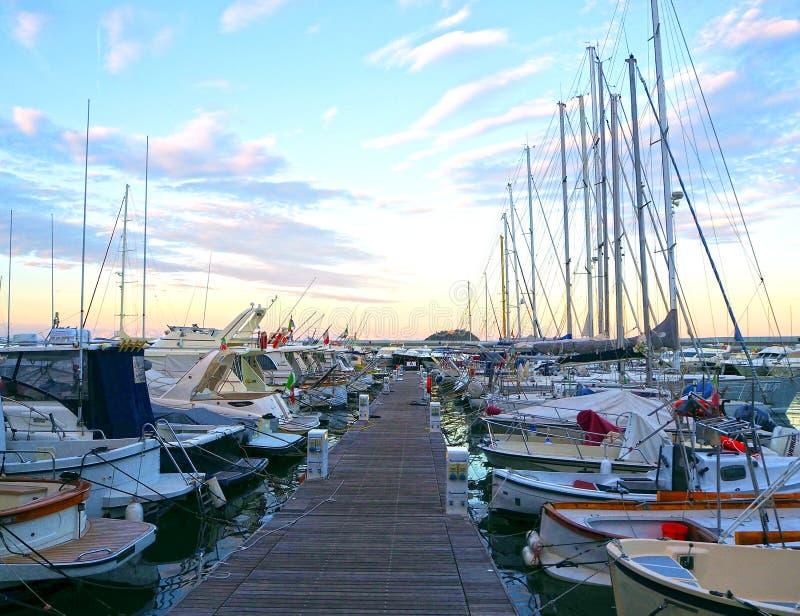 Luxejachten en zeilboten in zeehaven bij zonsondergang Marien parkeren van moderne motorboten in Ligurië, Italië stock afbeeldingen