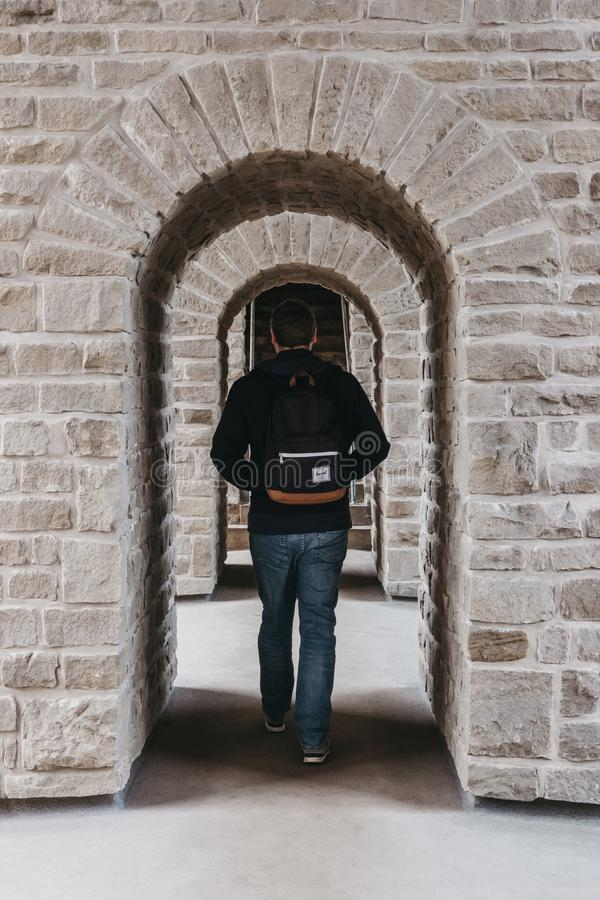 Rear view of man walking through arcs in Bock Casemates, Luxembourg City royalty free stock image