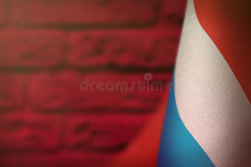 Luxembourg flag for honour of veterans day or memorial day. Glory to the Luxembourg heroes of war concept on red blurred painted. Luxembourg hanging flag for royalty free illustration