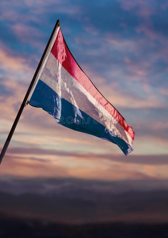 Luxembourg flag waving on sky at dusk stock images