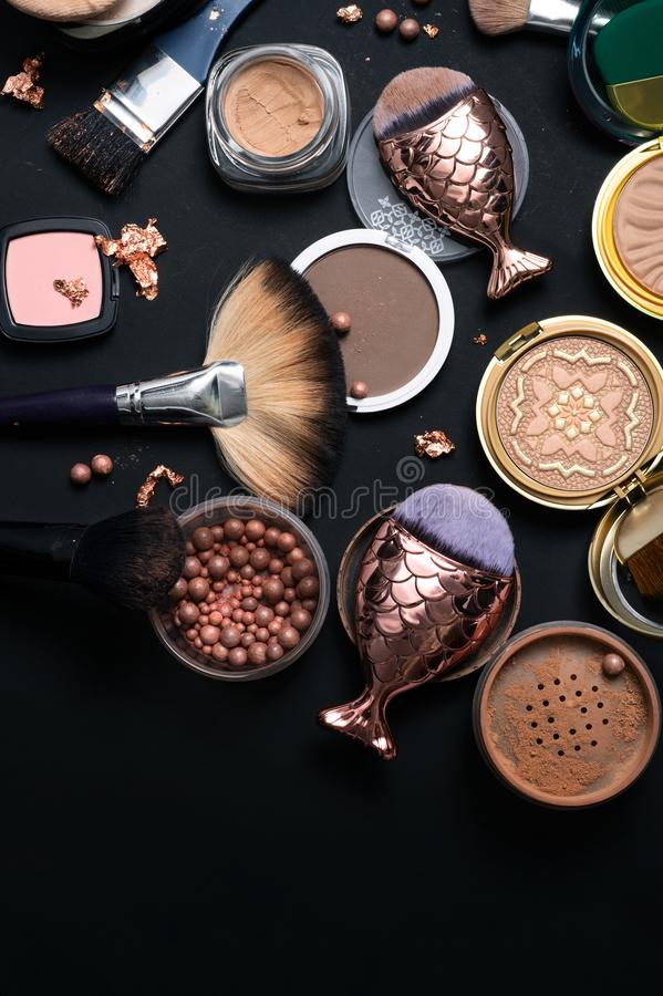 Luxery Set of bronze powder with makeup brushes on black backgro. Und stock photo