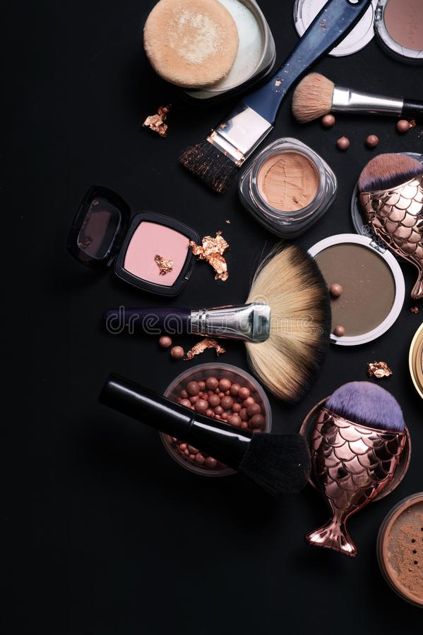 Luxery Set of bronze powder with makeup brushes on black backgro. Und royalty free stock photos
