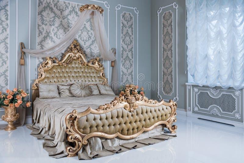 Luxeslaapkamer in lichte kleuren met gouden meubilairdetails Groot comfortabel dubbel koninklijk bed in elegante schrijver uit de royalty-vrije stock fotografie