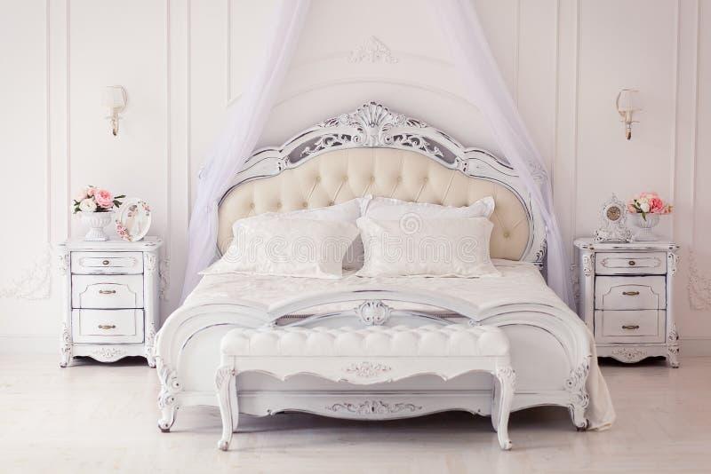 Luxeslaapkamer in lichte kleuren met gouden meubilairdetails Groot comfortabel dubbel koninklijk bed in elegante schrijver uit de stock afbeeldingen
