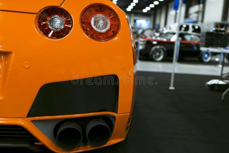 Luxesportwagen De achtermening van een oranje luxesportwagen uitlaatsysteem Moderne Sportwagen buitendetails royalty-vrije stock afbeelding