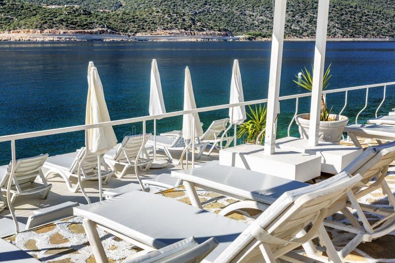 Luxestrand in een mooie baai met witte ligstoelen Prachtige meningen van het overzees en de bergen op een zonnige dag royalty-vrije stock foto's