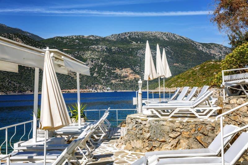 Luxestrand met witte zonlanterfanters en paraplu's in een mooie baai Schitterend landschap royalty-vrije stock foto's