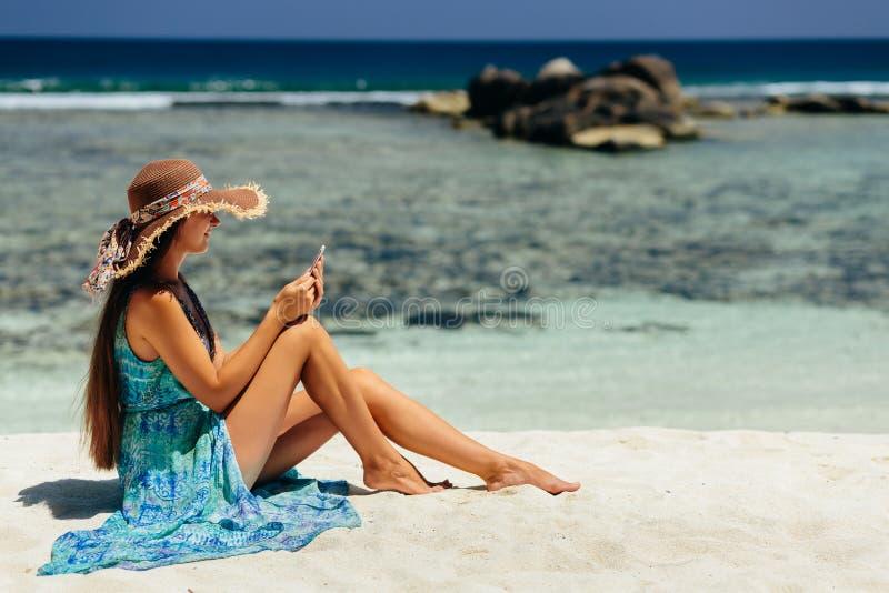 Luxevrouw die smartphone op strand gebruiken stock foto