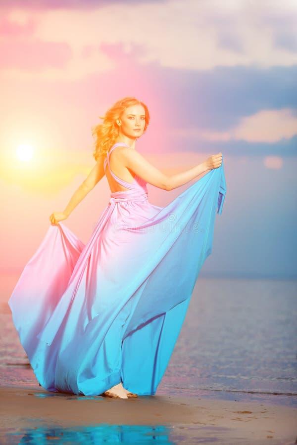 Luxevrouw in een lange blauwe avondjurk op het strand schoonheid stock foto