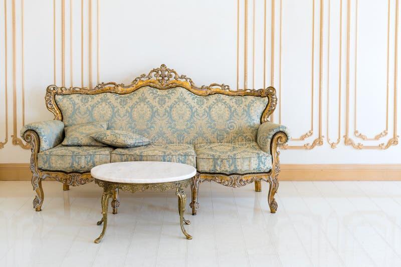Luxewoonkamer in lichte kleuren met gouden meubilairdetails Elegant klassiek binnenland royalty-vrije stock afbeeldingen