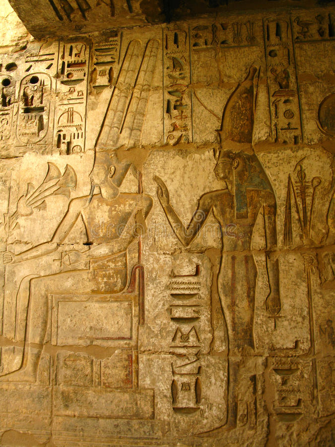 Luxor: carvings of pharaoh and wife, Medinet Habu. Luxor: stone carvings of the pharaoh and his wife surrounded by hieroglyphs, in Medinet Habu temple, dedicated stock photos