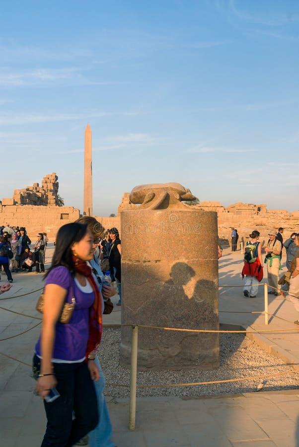 Luxor, Egipto 20 de fevereiro de 2017: Turistas fêmeas novos que circundam em torno do besouro sagrado em Templo de Luxor De acor foto de stock
