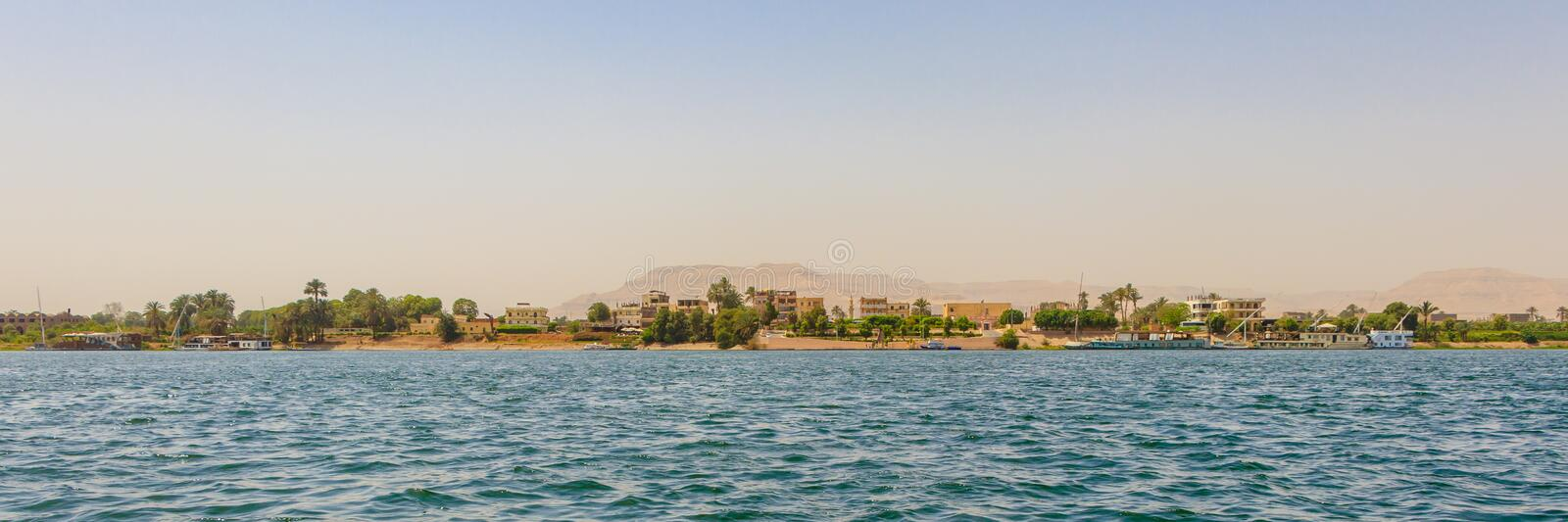 Residential buildings on the Nile river with sailboats in Luxor, Egypt. Nile River is the longest river in the world, called the father of African rivers. It stock photography