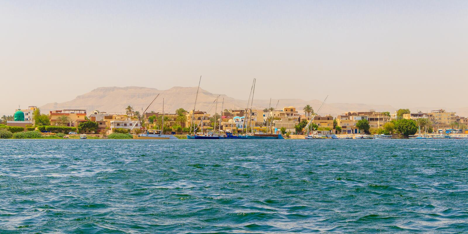 Residential buildings on the Nile river with sailboats in Luxor, Egypt. Nile River is the longest river in the world, called the father of African rivers. Its stock photography