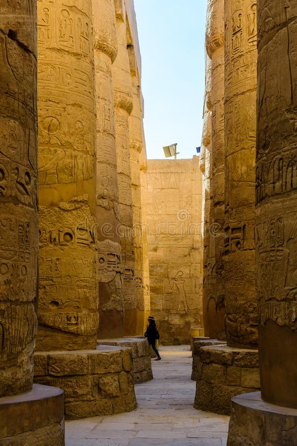 Lonely woman figure among the columns in the great hypostyle hall of the Karnak temple royalty free stock photography